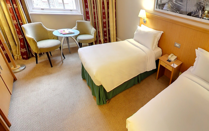 Two single white beds in a hotel room, with two chairs and a table in the background