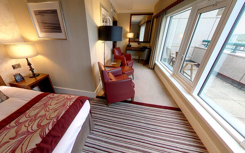 A double bed and two red chairs in a hotel room, facing out to a balcony