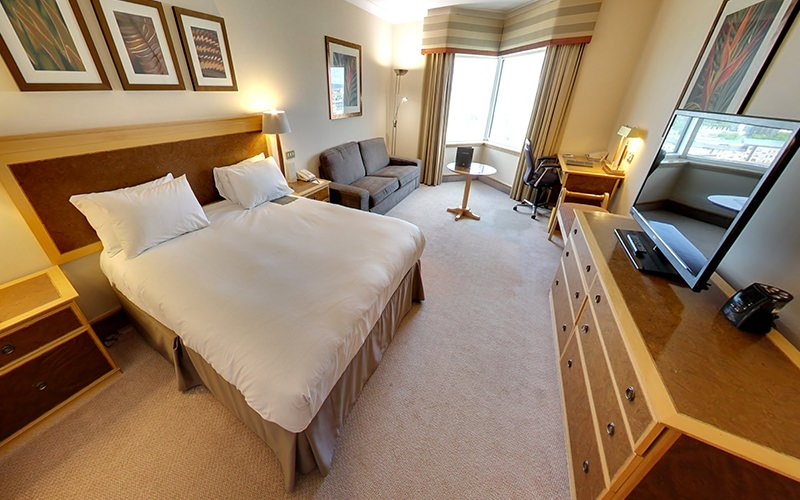 A double bed in a hotel bedroom, facing a set of drawers with a TV on top, with a bedside table, sofa and desk in the back