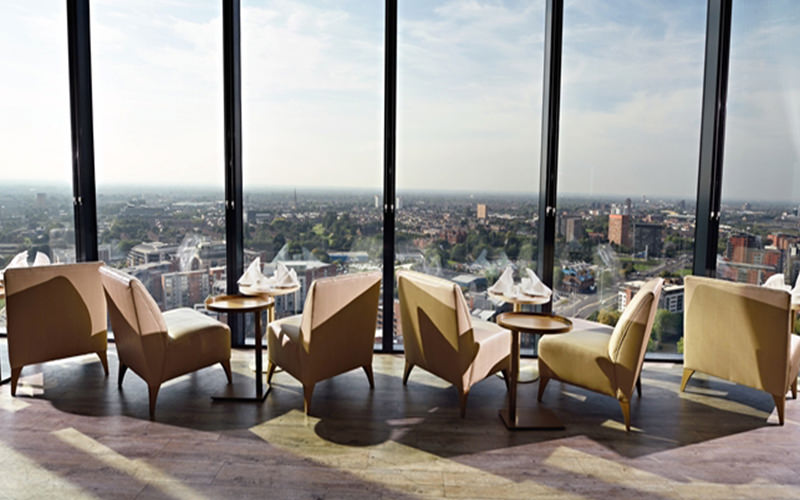 Tables and chairs alongside floor to ceiling windows, overlooking the Manchester skyline