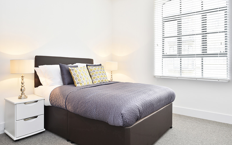 A double bed in the centre of a white room, alongisde a white bedside table