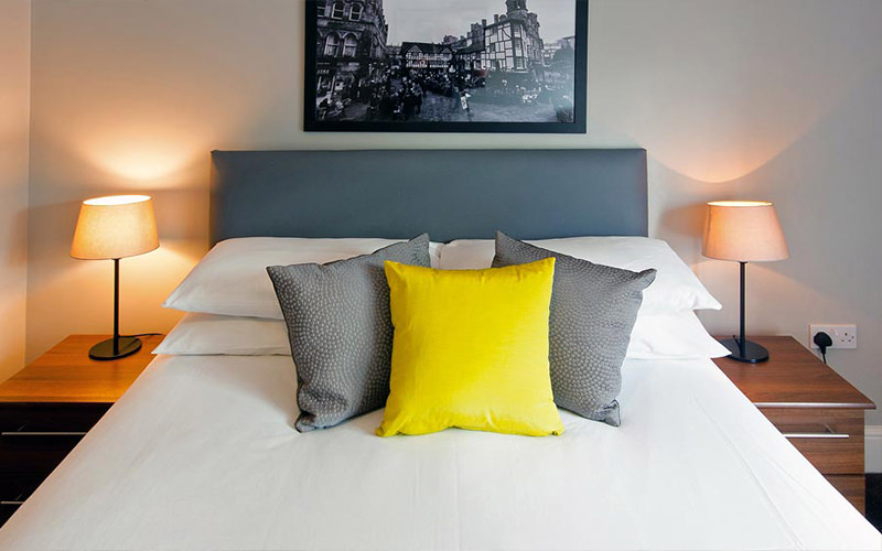 A double bed with grey and yellow cushions on top, underneath a black and white picture hanging on the wall
