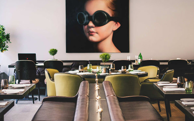 The dining area in Courtyard by Marriott, with a picture of a little girl with goggles on, mounted on the wall