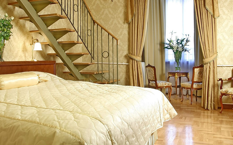 A bedroom with a staircase running above it