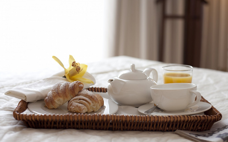 Croissants and tea on a basket tray, laid out on a bed