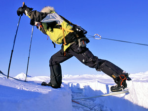 A man on skis in the North Pole streching to get over a crevasse.