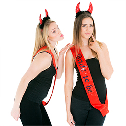 Two girls wearing devil horns