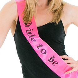 A hot pink bride to be sash modelled with a mini hat