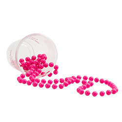 A shot glass on the side with pink beaded necklace laid out in front of it