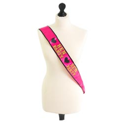 A pink and gold hen party sash on a mannequin