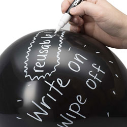 A hand using a white pen to write on a black, inflated balloon
