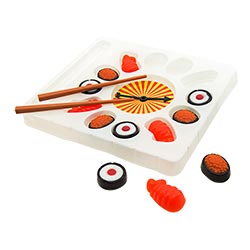Some sushi style sweets with two chopsticks and three sweets lying out