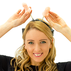A girl wearing willy headboppers and pointing to them