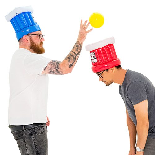Two guys playing human beer pong.