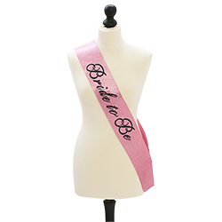 A pink and glittery bride to be sash on a mannequin