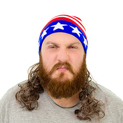 A man looking angry and wearing a stars and stripes hat with a mullet attached