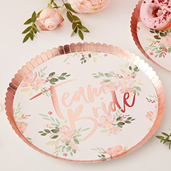 paper plates seen on a table with flowers.