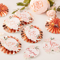 A selection of the floral team bride badges on a table.