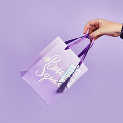 Somebody holding the gift bag by the purple ribbon.