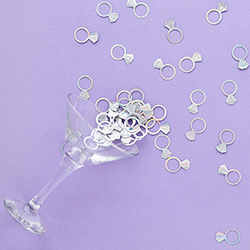 Diamond ring confetti on purple background.