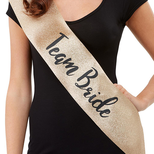 The gold sash modelled by someone wearing a black top.