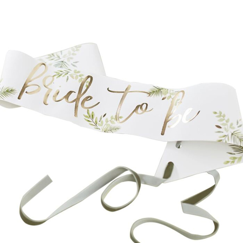 Bride to be sash with gold writing seen with some plants.