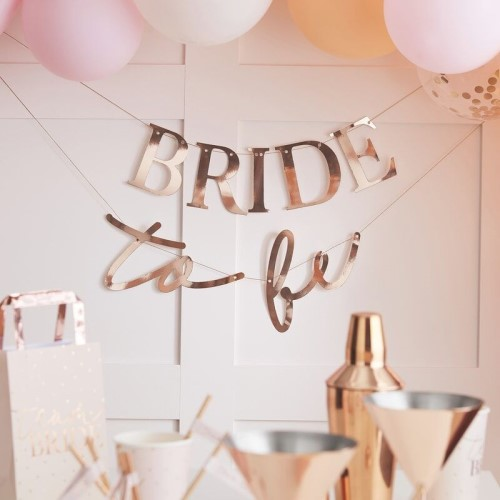 The bride to be banner against a wall with other decorations.