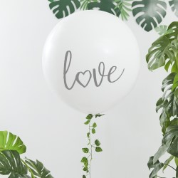Huge white Love Balloon with plants in the background.