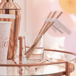 The rose gold straws seen in a glass.