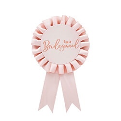 Rose gold bridesmaid rosette badge against a white background.