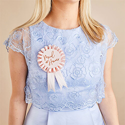 The rosette worn by a girl in a blue dress.