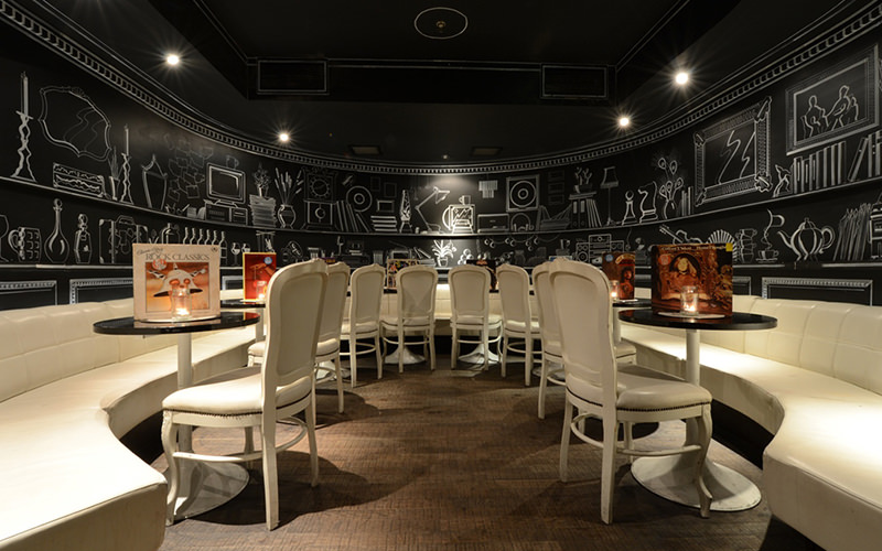 Dining room, with white chairs and tables, set in front of black walls with white sketches, at Foundation, London