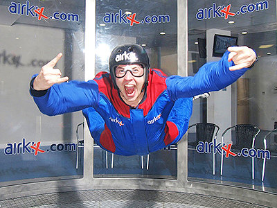 A man indoor skydiving, wearing blue and red overalls, a helmet and goggles