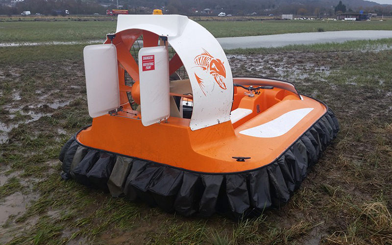 The back of a stationary orange hovercraft on a muddy field