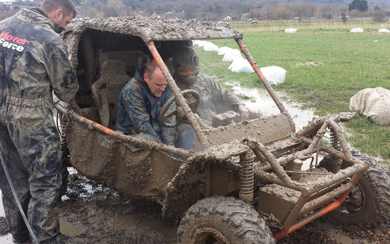 Two men in a muddy dirt buggy, with a man standing next to the vehicle