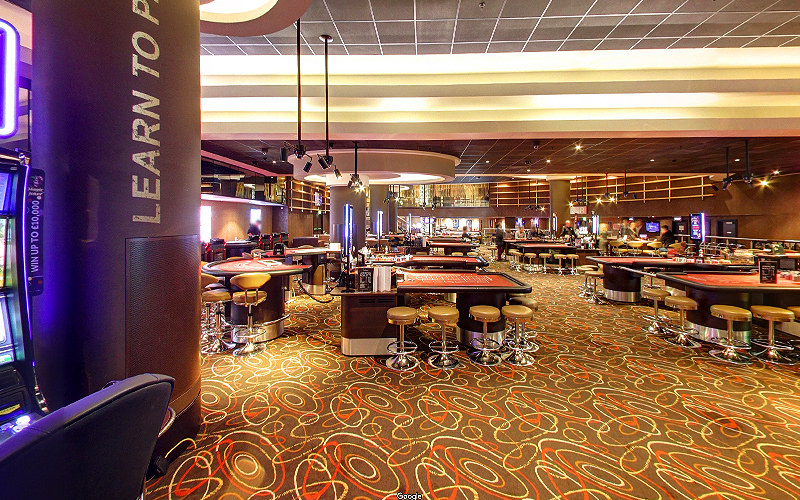 The interiors of Manchester's Genting Casino, showing poker tables and stools