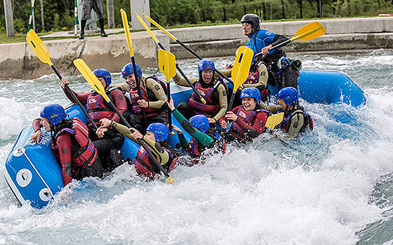 A raft full of people on a white water rafting course