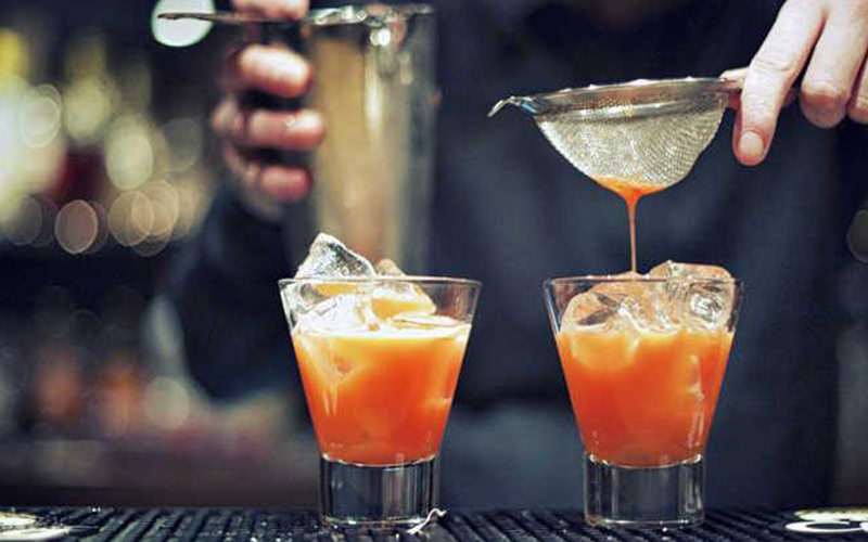 Two orange cocktails with a man holding a strainer above one
