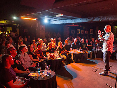 A stand up comedian performing to an audience in Laughterhouse, Liverpool
