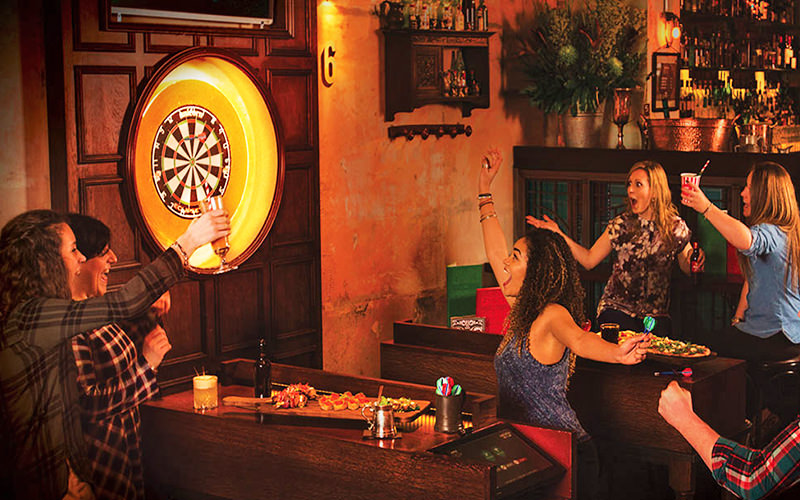 People cheering and looking at an electrical dartboard on the wall