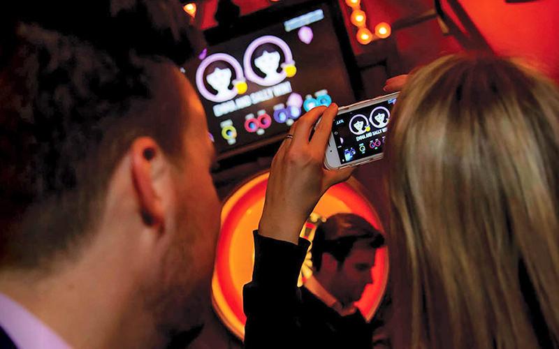 electronic darts scoreboard, woman taking photo on an iPhone