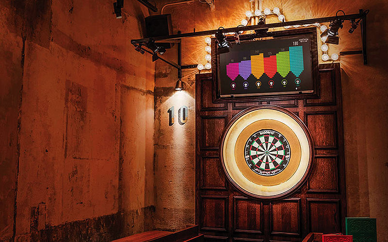An electrical dartboard on a wooden wall