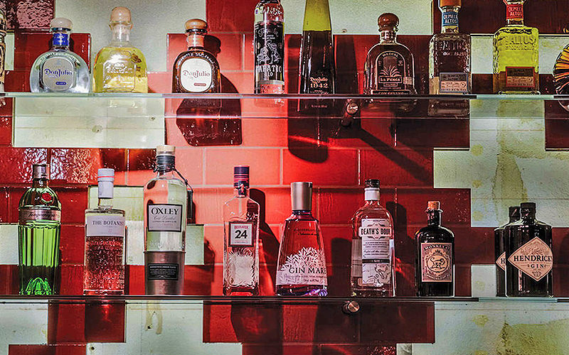 Bottles of spirits lined up on shelves on a red and white wall