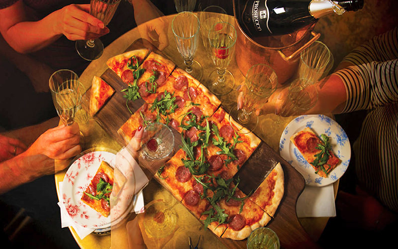Birds eye view of pizza on a table with four people eating