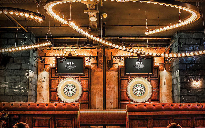 Two dartboards on a wooden wall, surrounded by bright lights, at Flight Club, London