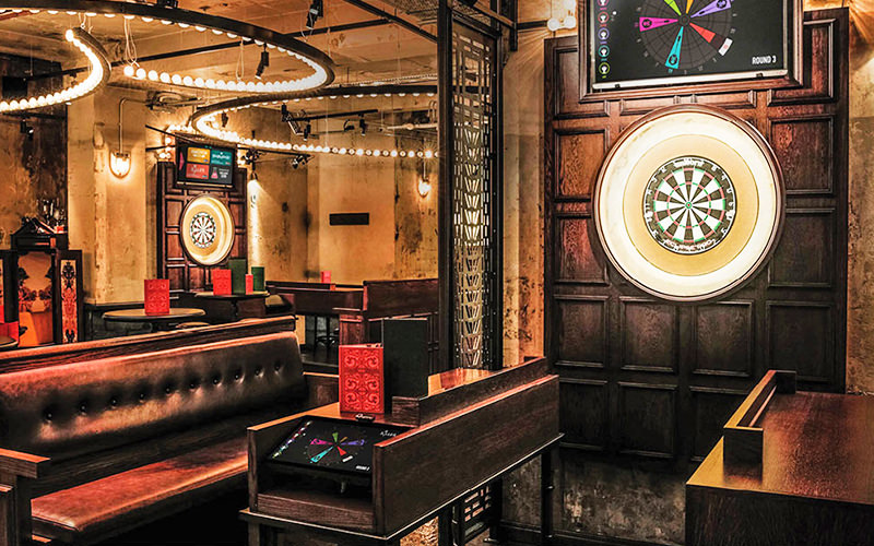Electrical dartboards on a wall, with leather booths surrounding them, at Flight Club, London