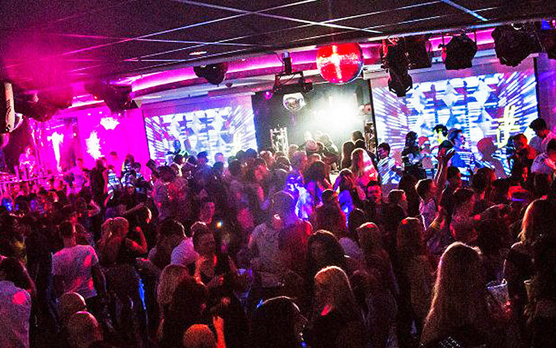 Men and women in a busy club room, with a backdrop of pink lighting