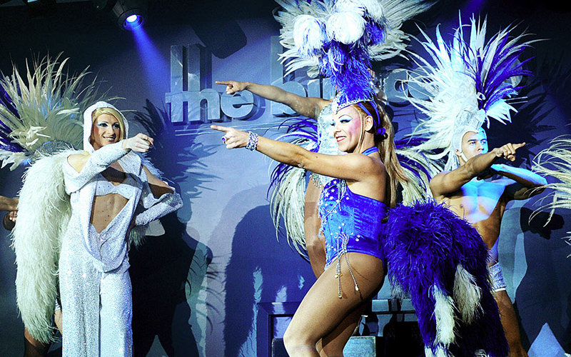 Three men on stage in feathered headdresses and costumes pointing in front of them