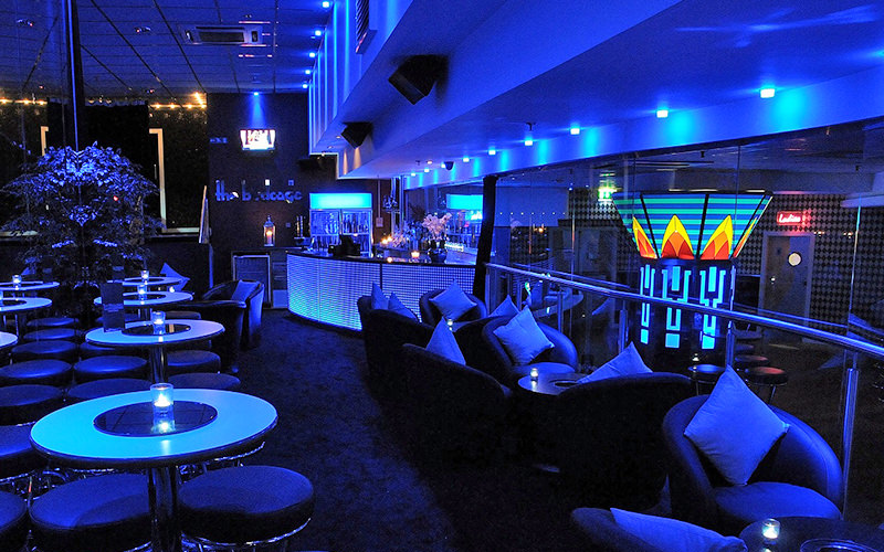A blue lit club rooom with tables and stools along the right side, and leather chairs along the left side