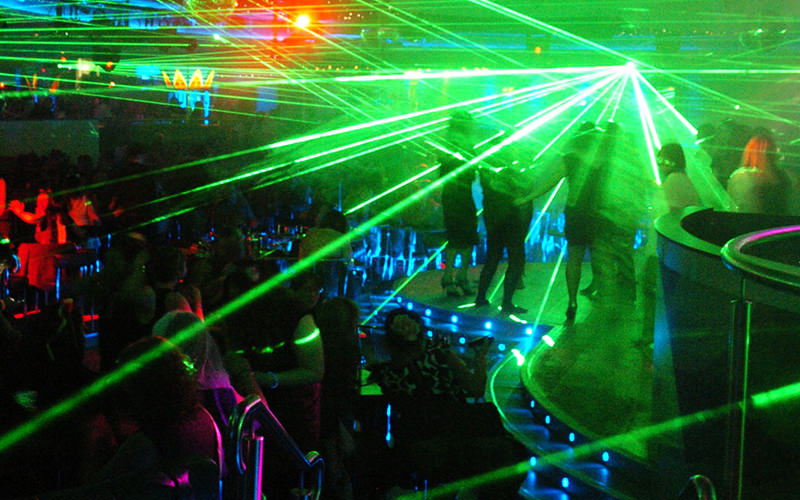 Men and women dancing with green laser strobes